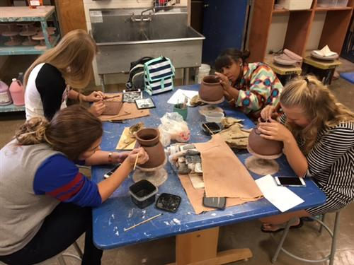 Ceramics II students painting Native American Vessels